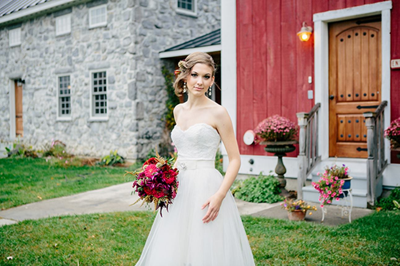 A bride in front of the Stone House at The Inn at Grace Farm Inn